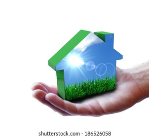 Nature and renewable energy concept with a man hand holding a green house icon with grass, blue sky and sun rays. Isolated on white background.