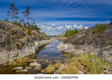 Nature of Russia. Karelia. Rocky coast of the island. Pine trees grow on a stony shore. Nature of Karelia. The shore of Lake Ladoga. The reserved places of Russia. The nature reserve.