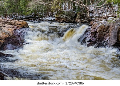 Nature Scene featuring beautiful waterfalls showing water streaming through rock crevices on a sunny day