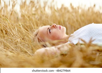 nature, summer holidays, vacation and people concept - young woman or teenage girl lying and dreaming on cereal field