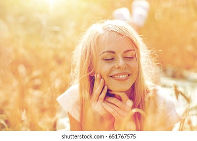 nature, summer holidays, vacation and people concept - happy smiling woman or teenage girl lying cereal field