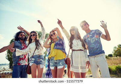 nature, summer, youth culture and people concept - happy young hippie friends dancing outdoors