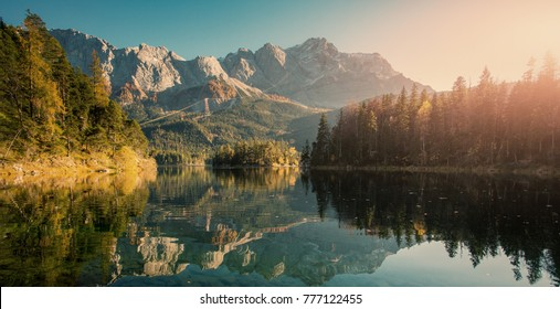 Nature sunny landscape in sunset. Dramatic Picturesque scene. The Alps reflected in water at sunset. Alpine landscape. Impressive autumn Landscape. View of Zugspitze from Eibsee, Instagram Effect.