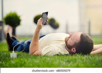 Nature and technology. A man with a beard lies on a green grass with a smartphone in his hands is charging power bank