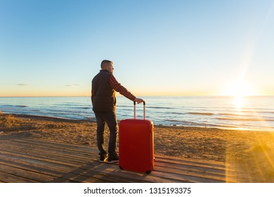Nature, travel, people concept - a man standing near the sea with red suitcase