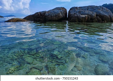 Nature view from the Perhentian Island beach. Coral can be seen under the sea with beautiful nature carved rock