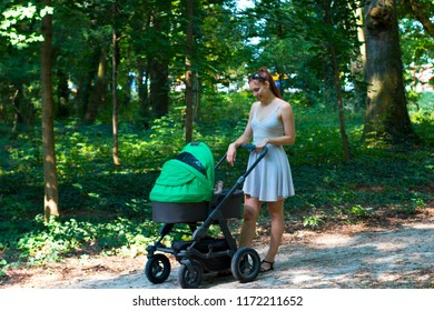 Nature walk with stroller, young mother in beautiful dress walking on the forest walkway with her baby in the pram, enjoying fresh air and smiling on her cute newborn, mother and baby stroller walk