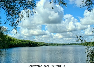 Nature, water, environment and paysage concept-lake landscape with forest view on the horizon and blue sky with white clouds.Lake Mare a Goriaux France.