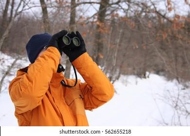 Nature & Wildlife: A birdwatcher looking through binocular on snowy background