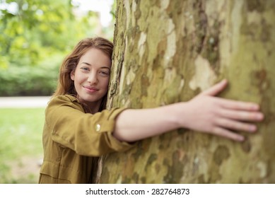 Nature-Lover Blond Teen Girl Hugging Huge Tree Trunk at the Park While Smiling at the Camera.