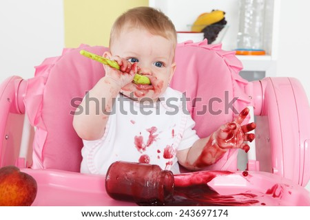 Naughty baby eating alone in the high chair