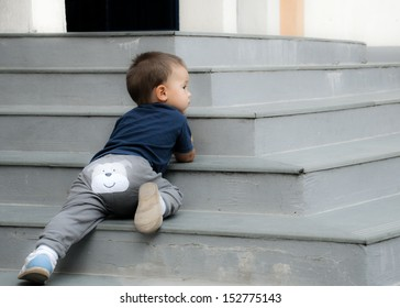 Naughty baby lying on the stairs outdoor