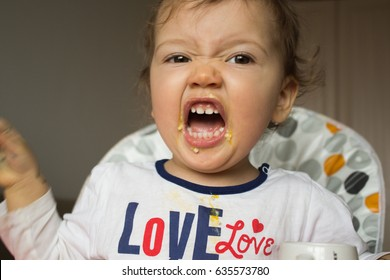 A naughty child does not want to eat. The kid is stained with porridge. Screaming child