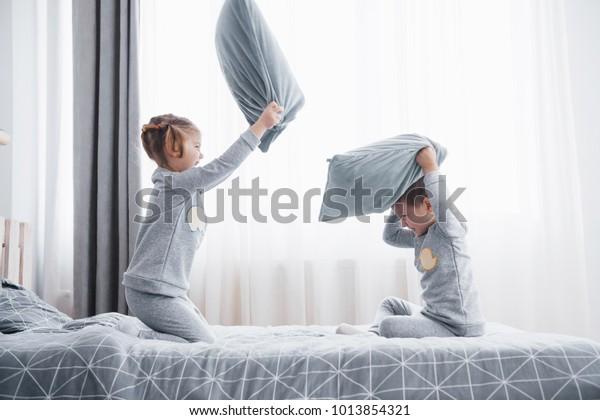 Kinderschänder Kleiner Junge und Mädchen spielten einen Kissenkampf auf dem Bett im Schlafzimmer. Sie mögen diese Art von Spiel.