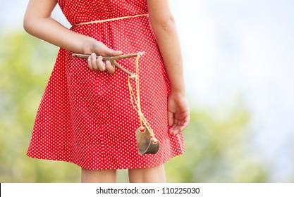 Naughty girl hiding slingshot behind her back