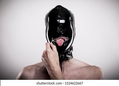 Der unartige Mann mit glänzender schwarzer Gummimaske auf dem Kopf öffnet den Reißverschluss aus Metall, um seine Zunge auszustrecken. Porträt von Unterwürfen mit latexfarbenem Blind, einzeln auf Hintergrund.