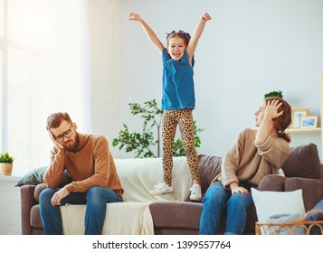 naughty, mischievous, child girl jumping, laughing and having fun, parents stressed with a headache