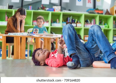 naughty preschool does not pay attention to the class with upset and disappointed dizziness of the teacher in background