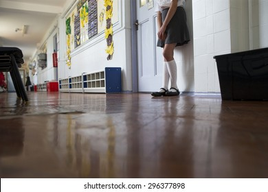 Naughty school girl stands in the corridor after being sent out of class.