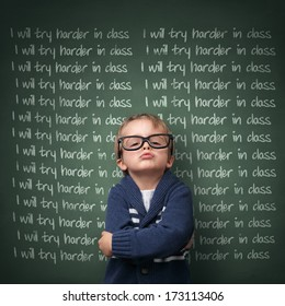 Naughty schoolboy with lines written on a blackboard reading I will try harder in class. Detention and school discipline / punishment concept