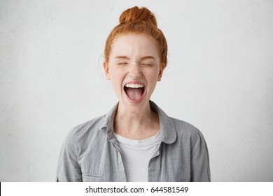 Naughty spoiled teenage girl with ginger hair went into hysterics after mother didn't allow her to go out with friends, closing eyes tight and opening mouth in shriek expressing protest, disobedience