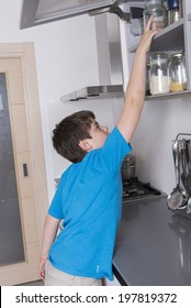 naughty young boy taking candy from a high kitchen cabinet