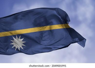 Nauru flag isolated on the blue sky with clipping path. close up waving flag of Nauru. flag symbols of Nauru.