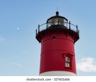 Nauset Light, the iconic red and white landmark lighthouse, Eastham Cape Cod Massachusetts USA with moon early evening. Copy space in blue sky. The beacon is a symbol of strength.