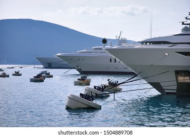 Nautical background with few luxury super yachts standing moored in a closed bay