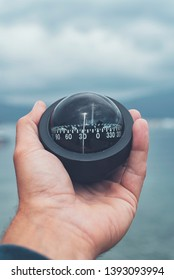 Nautical compass in man's hand