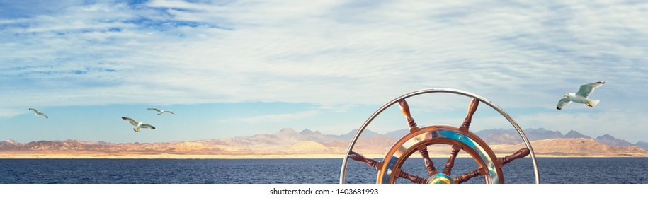 Nautical concept with wild seashore, mountains and flying gulls. Marine landscape with steering wheel on yacht, rocky coast and seagulls over the sea - wide panorama about your sea adventures.