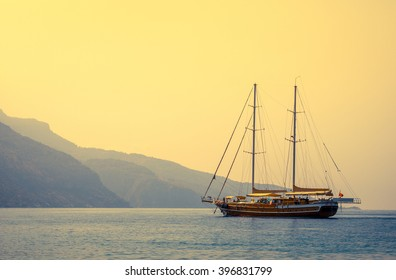 Nautical landscape with retro sailboat at sunset. Sea voyage on sailing yacht - luxury lifestyle in summer. Seashore with sailing vessel near islands, soft light effect.