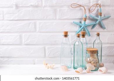 Nautische Dekorationen oder Marmordekorationen in der Nähe der weißen Ziegelwand. Dekorative blaue Sternfische, blaue Flaschen mit Muscheln. Selektiver Fokus. Platz für Text.