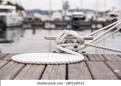 Nautical mooring line rope on the jetty. Curled mooring line.