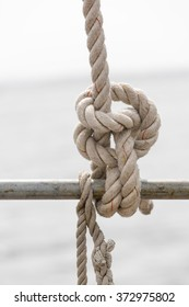 Nautical rope knot on a vintage sailboat at sea. Maritime background with copy space. Neutral colors