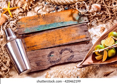 Nautical Themed Background with Copyspace - Cocktail Shaker, Limes and Blank Planks of Weathered Wood on Sand Surrounded by Fishing Net and Seashells