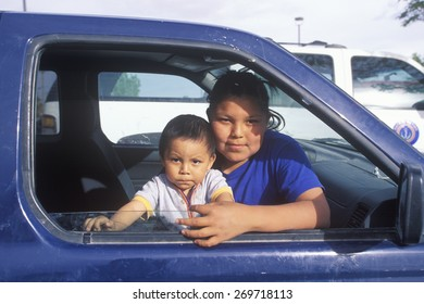 Navajo teenage girl and baby looking out of car window, Kayenta, AZ