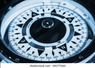 Naval compass. Blue toned monochrome macro photo