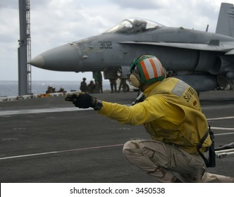 A Naval Officer signals for an F-18 Hornet to launch on board an aircraft carrier