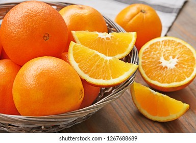 A lot of Navel Orange full and slice in basket on wooden background.