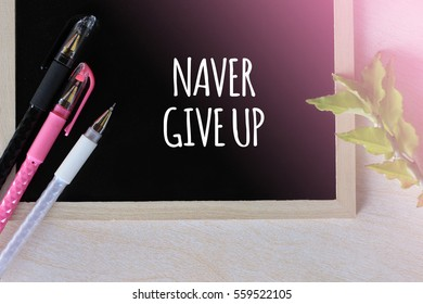 NAVER GIVE UP - positive word on blackboard concept with pen and green leaf on wooden background