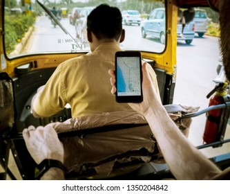 Navi Mumbai, Vashi, Maharashtra, India - March 16, 2019: Passenger view of a man using an Uber app from a rickshaw/tuktuk taxi