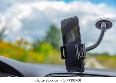 Navigating outdoors concept. Smartphone in the protective case attached to the front glass of a car with a suction cup holder. Screen of the phone has copy space for mockups.