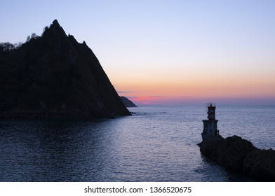 Navigation lighthouse with the sea at sunset