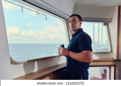 Navigation offcier / Pilot on the bridge of a ship underway with bicnocular and radio. Line of horizon and beautiful clouds on a background.