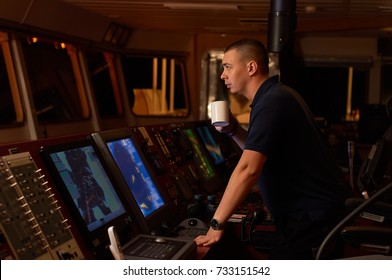 Navigation officer / Pilot on bridge of a vessel underway with cup of coffee in hands