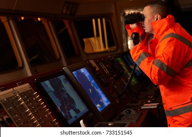 Navigation officer / Pilot on bridge of a vessel underway with radio station and binocular in hands