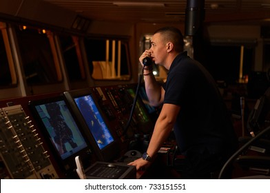 Navigation officer / Pilot on bridge of a vessel underway with radio station in hands