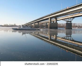 Navigation on a big river. Ship under bridge.
