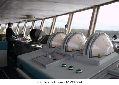 Navigational officer driving the ship on the river. Wide shot.
